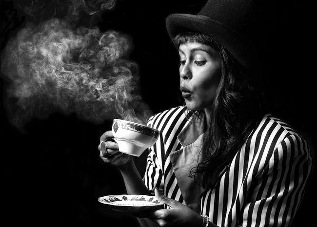 """some like it hot"". Black & White Tea Tea Time Haze Steam Smoke Blackandwhite Showcase August Portrait Of A Woman Woman The Week Of Eyeem Portrait Sonnenallee Neukölln TeaCup Blowing Away Monochrome Canon Canonphotography Eyeemphoto Funny Top Hat Studio Shot Black Background The Magic Mission"