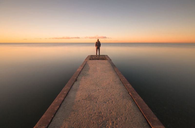 Man Standing On Jetty Against Sky During Sunset