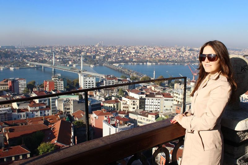 Smiling Woman Looking At City With Golden Horn Metro Bridge In Background Against Clear Blue Sky