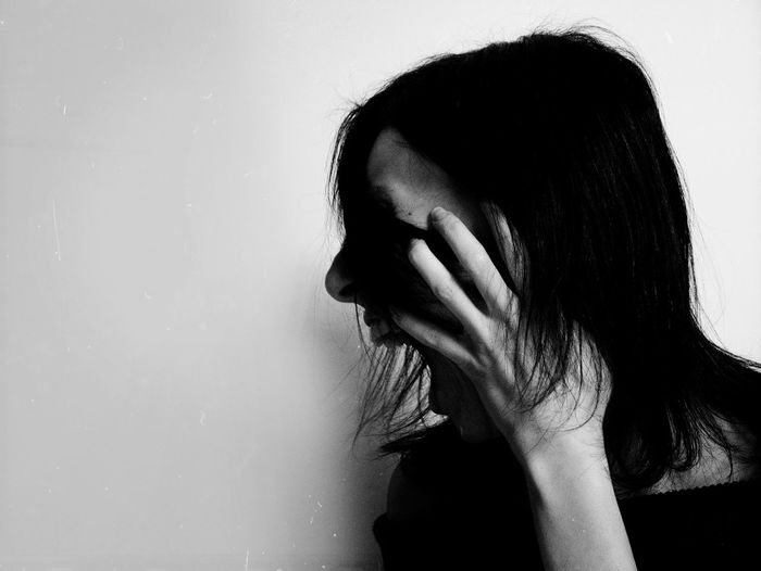 Portrait of woman covering face against white background