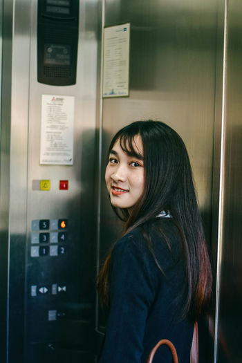 Portrait of young woman standing inside elevator in building