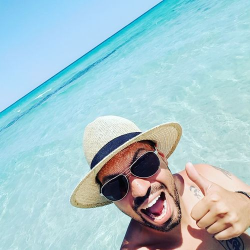 Portrait of man wearing sunglasses and hat in sea during summer