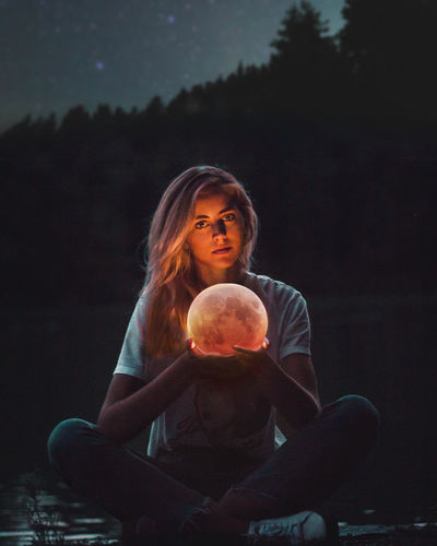 Digital Composite Image Of Young Woman Holding Moon Against Black Background