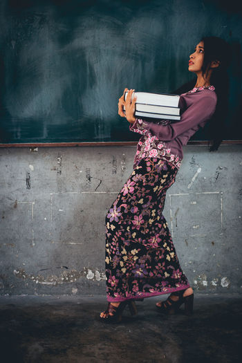 Side view of woman carrying books while walking against blackboard in classroom
