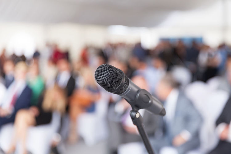 Microphone in focus against blurred audience at a professional conference. Celebration Corporate Event Microphone Head PR Press Speech Auditorium Business Business Conference Communication Corporate Business Crowd Focus On Foreground Input Device Large Group Of People Marketing Media Meeting Microphone Microphone Stand News Public Relations Real People Speech Talking