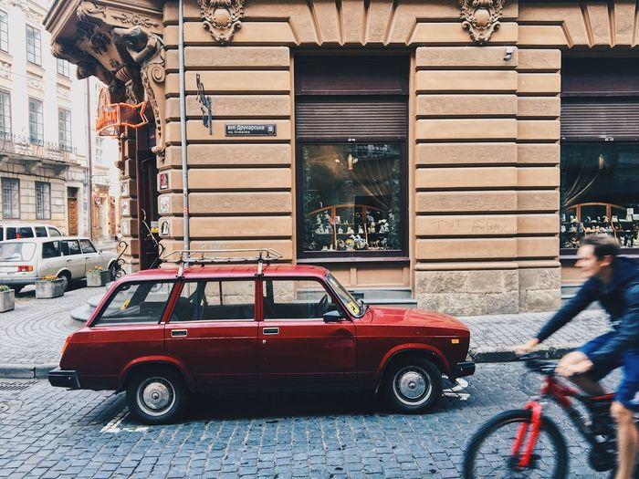 Vintage car on street against buildings in city