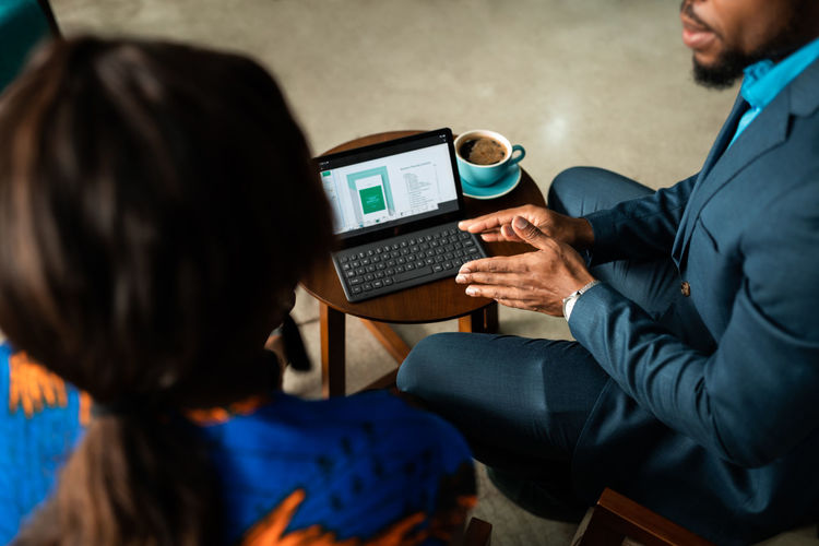 Midsection of businessman wearing suit using laptop having discussion with colleague while sitting at office