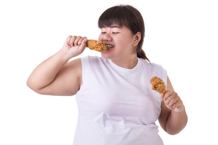 Full length of a girl eating food against white background
