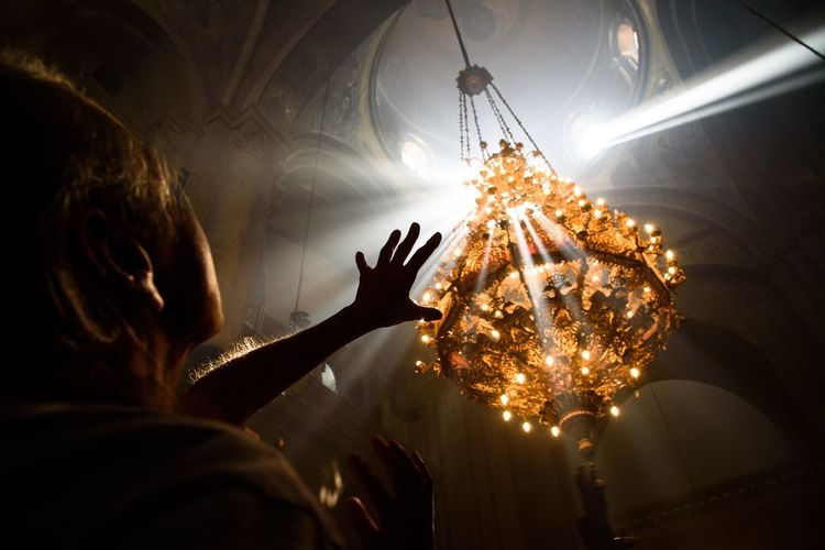 Low angle view of illuminated chandelier in an old church