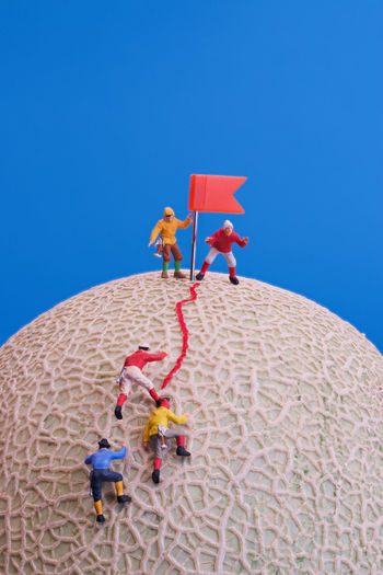 Low angle view of people against blue sky