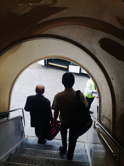 Airplane Airport Arch Bus Casual Clothing City Life Day Destination Full Length Journey Leisure Activity Lifestyles Men Rear View Transfer Walking Walkway