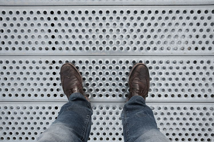 Low Section Of Man Standing Patterned Metallic Floor