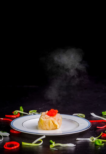 Close-up of cake on plate against black background