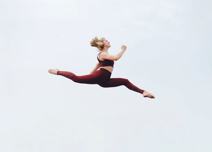 Low section of woman jumping against white background