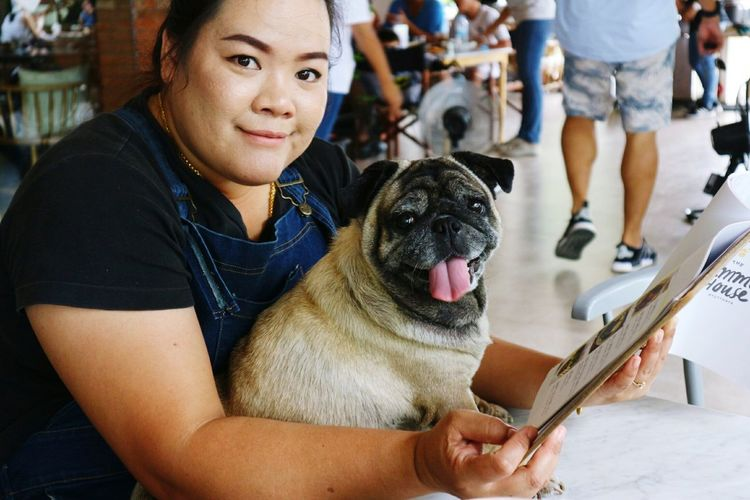 Portrait of woman with pug holding menu