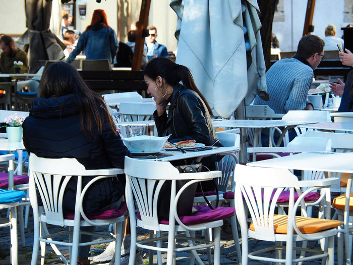 European Cities Real People Sitting Adult Casual Clothing Day Architecture Travel Destinations Travel Photography Street Photography Friends Daily Life European City Eastern Europe Cluj-Napoca Table Women Restaurant Rear View People Lifestyles Young Women Leisure Activity Romania