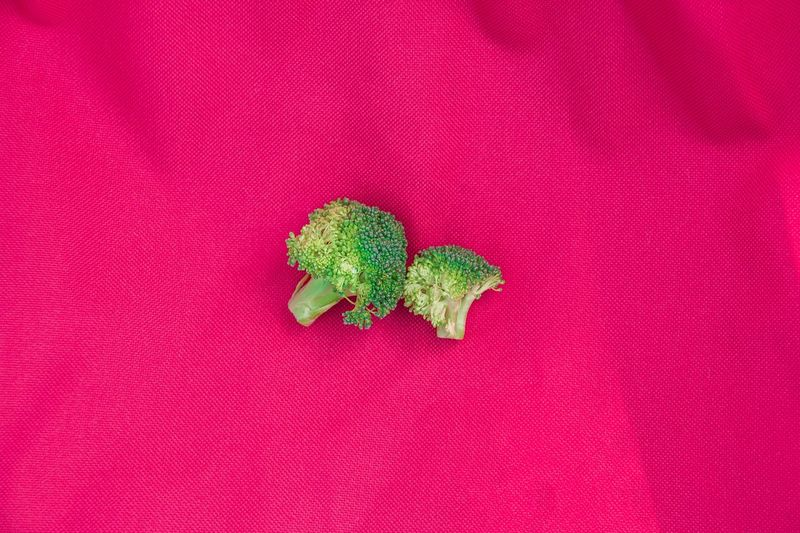 Directly above shot of broccolis on pink fabric