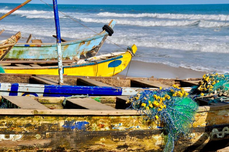 Fishing boats moored on beach against blue sky