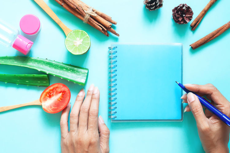 Cropped hands of woman writing in spiral notebook against blue background