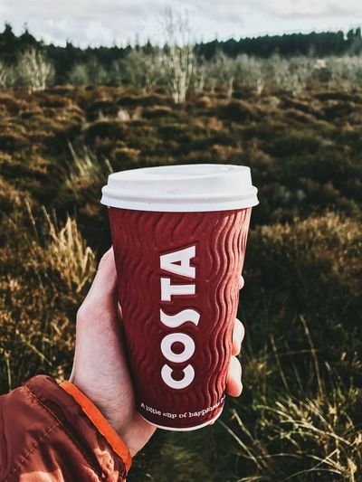 A person is pictured holding a Costa Coffee take away cup up outside in a forrest Costa Coffee Costa Takeaway Cup Take Away Coffee Cup Cardboard Cup Coffe Cup Cost Cup Holding Human Hand One Person Outdoors