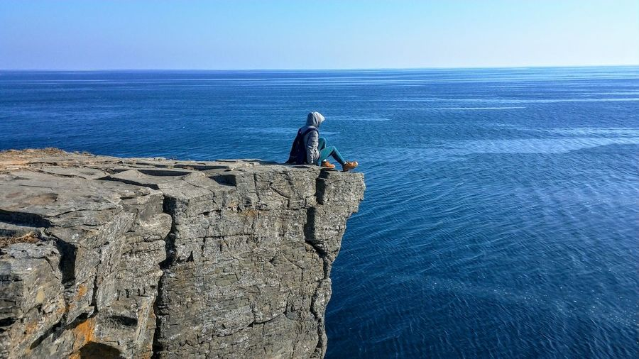 Side view of man on cliff against blue sky