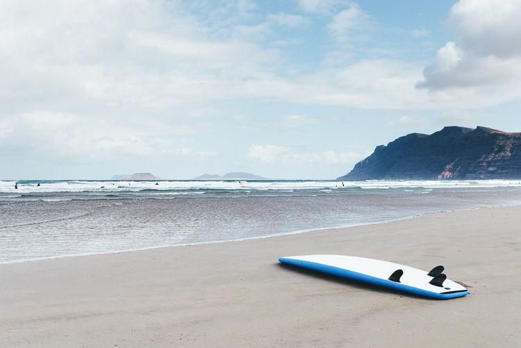 Surfboard at beach against sky