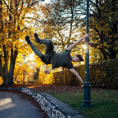 Full length of man hanging on pole during autumn