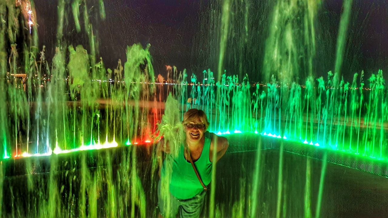 PORTRAIT OF SMILING YOUNG WOMAN STANDING IN ILLUMINATED WATER
