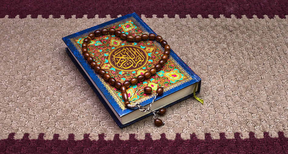 High angle view of beaded necklace with koran on carpet