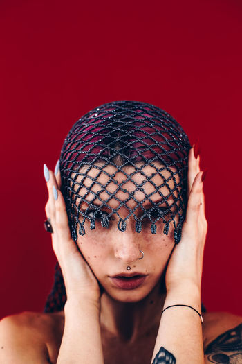 Close-Up Portrait Of Beautiful Woman Wearing Net Scarf Against Red Background