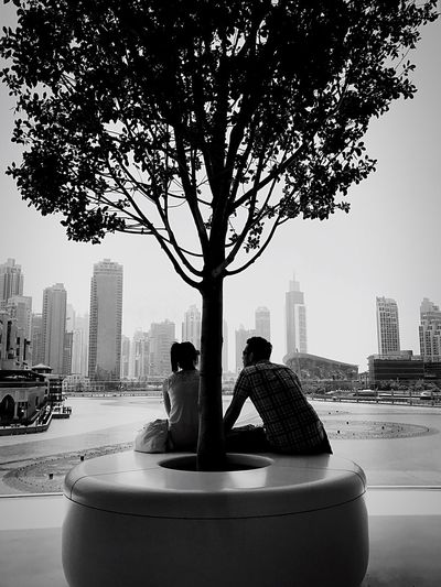 A 🌳 shared by 👫 City Tree Built Structure Architecture Two People Building Exterior City Life Men Transportation Sitting Urban Skyline Skyscraper Day Outdoors Real People Cityscape Togetherness Women Water Nature Neighborhood Map EyeEmNewHere