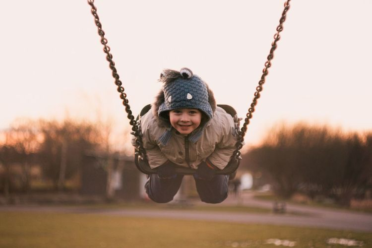 Childhood Warm Clothing Child Winter Enjoyment One Person My Best Photo Smiling Swing Leisure Activity Nature Fun Front View Cold Temperature Happiness Playground Looking At Camera Full Length Innocence Outdoors My Best Photo My Best Photo