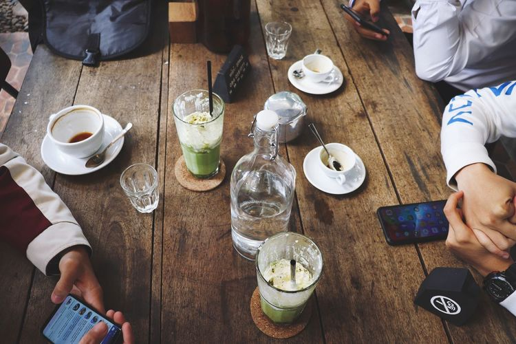 Friends having drinks while sitting at table in cafe