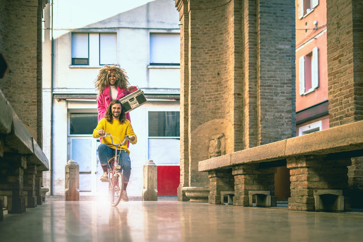 long hair young man riding a bicycle carrying on his afro-american friend. Mixed race friend having fun. She's carrying a big old vintage tape cassette recorder. Architecture Building Exterior Built Structure Real People Women Lifestyles Front View Adult Full Length City Day African American Woman Afro American African Descent Girl Fun Friendship Bycicle Carriage Carrying Outdoors Young Adult Adult Man Long Haired Man HaiRED Audio Cassette Cassette Player Vintage Old Antique Retro Leisure Activity Having Fun Friends Holding Taking Photos Moving Multicultural Multi Racial Tourism Tower Traditional Vacations Tape Happy Colorful Cheerful University