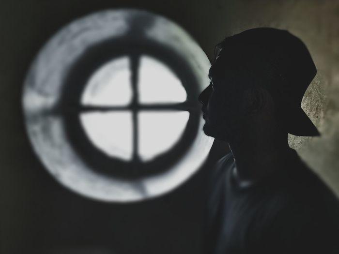 Portrait of silhouette boy standing against window