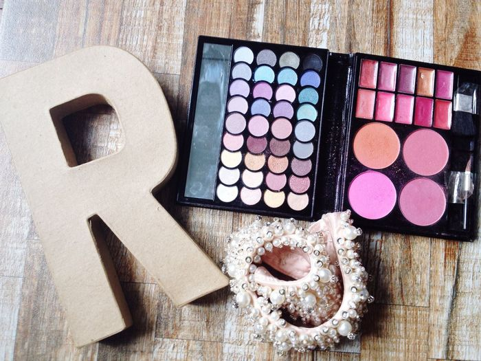High angle view of letter r with make-up kit on table