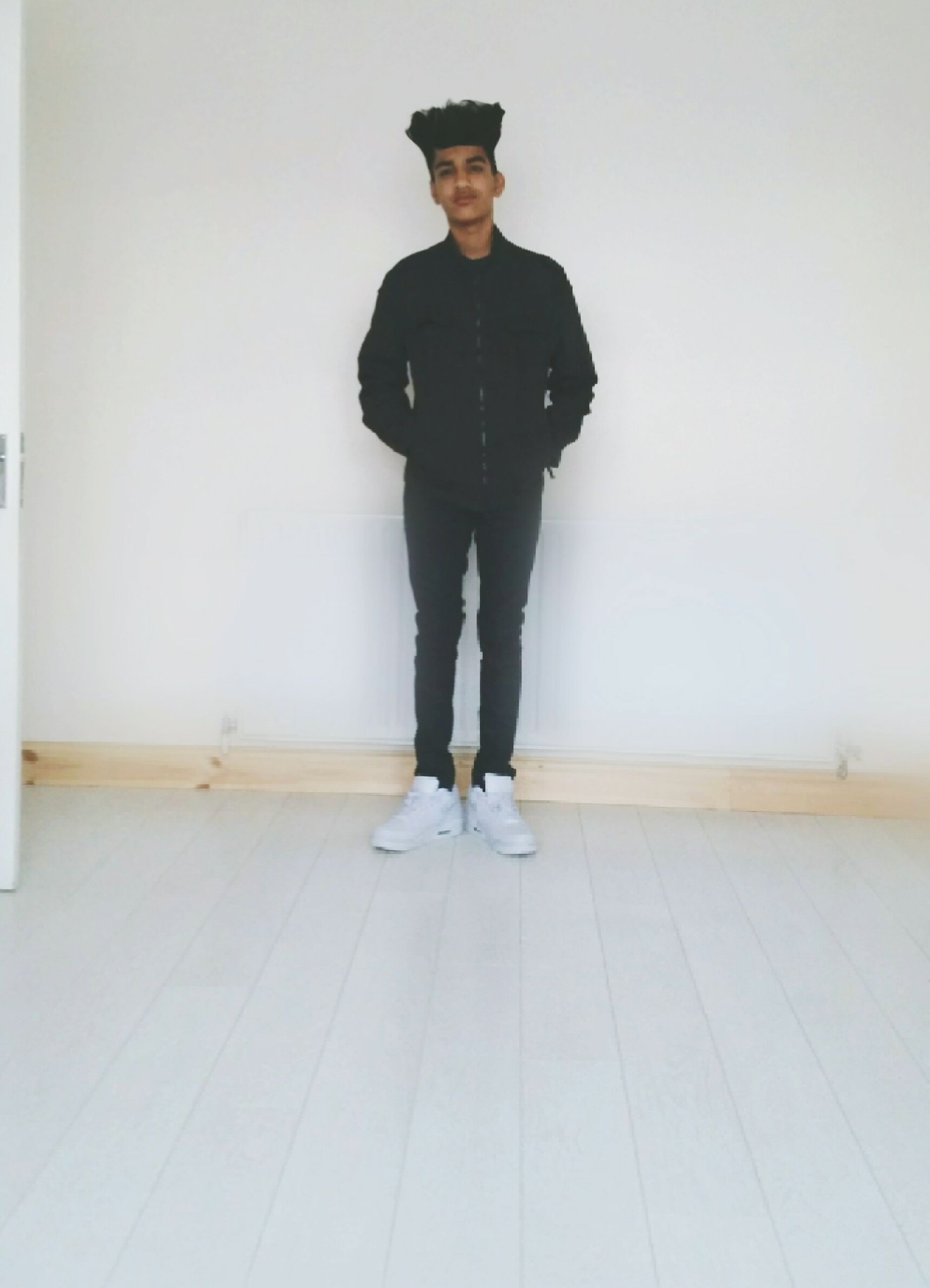 young adult, standing, indoors, lifestyles, casual clothing, front view, full length, wall - building feature, young men, leisure activity, looking at camera, portrait, person, three quarter length, copy space, wall, home interior