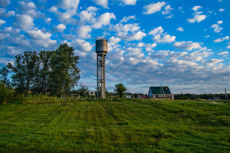 Water storage tank against cloudy sky
