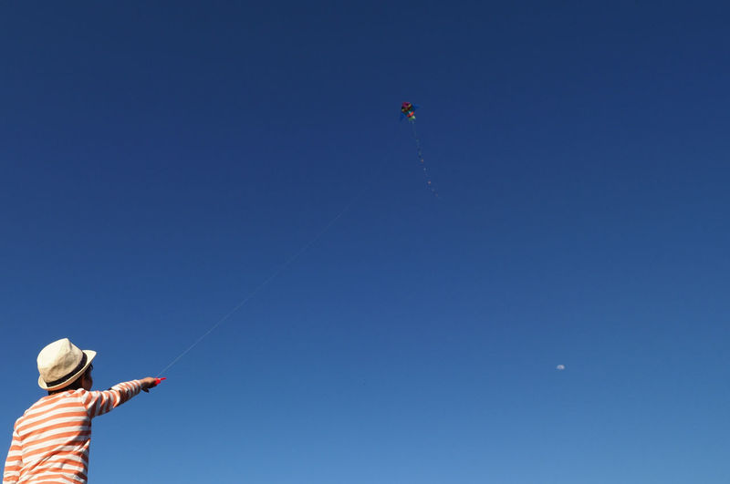 Low angle view of man flying kite against sky