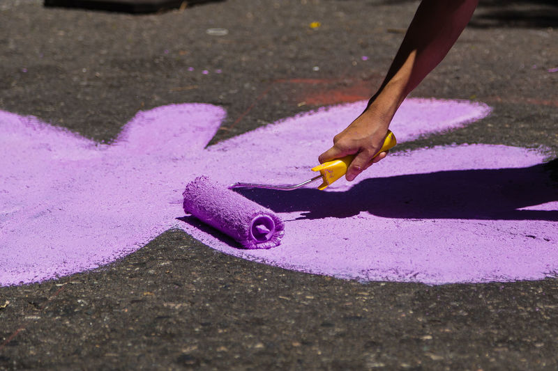 Paint Paint the Town Yellow Street Art/Graffiti Childhood Day High Angle View Holding Human Body Part Human Hand Lifestyles Low Section One Person Outdoors Paint Roller Painting Painting Street People Real People Shadow Violet Violet Flowers