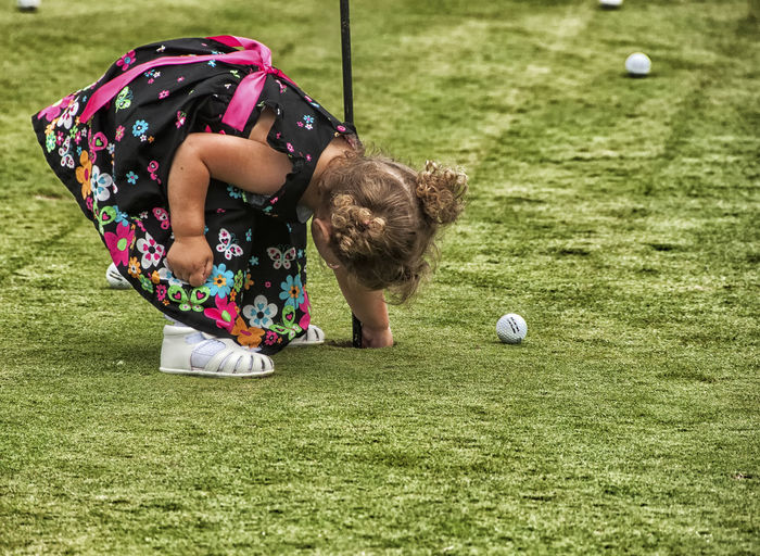 Girl with golf ball in grass