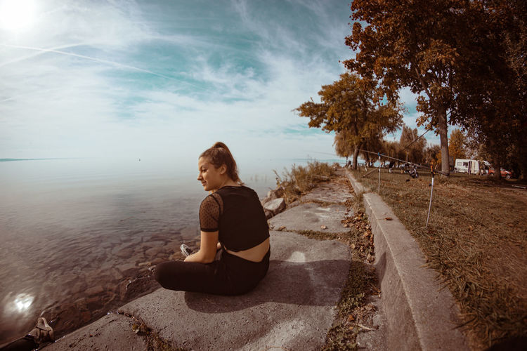 Full length of woman sitting on shore against sky