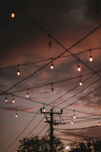 Low angle view of illuminated lights against sky at sunset