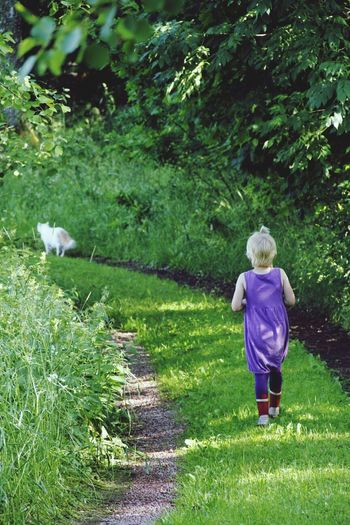 Young girl walking up grassy footpath