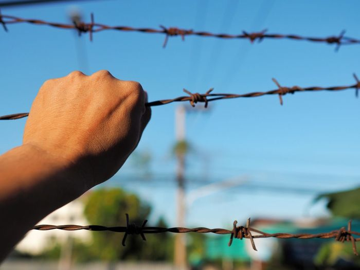 Close-up of hand holding barbed wire