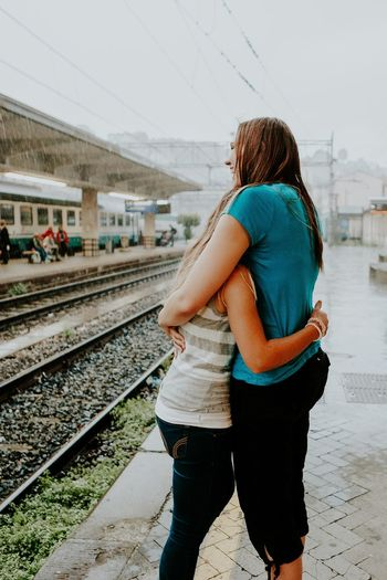 Happy Young Female Friends Embracing At Railroad Station During Monsoon