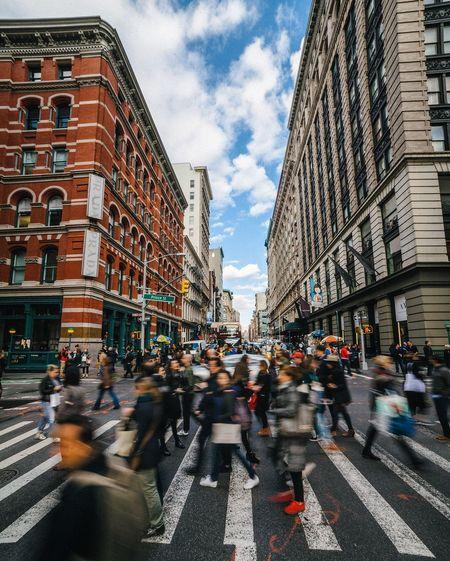Blurred motion of people walking on zebra crossing in city