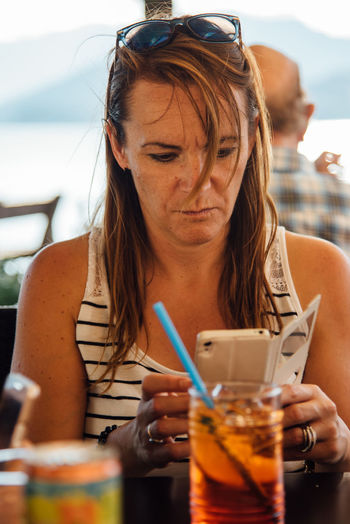 Woman Using Mobile Phone While Having Drink In Restaurant