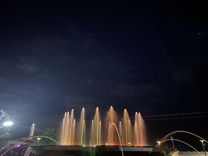 Low angle view of illuminated fountain against sky at night