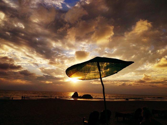 Beach umbrella against cloudy sky at sunset